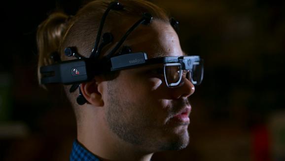Un casque EEG posé sur la tête d\'un homme qui regarde un écran à Toronto (Canada).