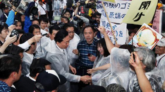 L'ancien Premier ministre Yukio Hatoyama sert la main d'unanti-nucléaire pendant une manifestation organisée devant la résidence du Premier ministre, occupée parKoshihiko Noda, le 20 juillet 2012.