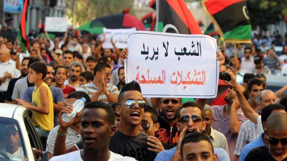 """Des manifestants libyenstiennent une pancarte : """"Le peuple ne veut pas de milices"""",dans les rues de Benghazi, le 21 septembre 2012."""