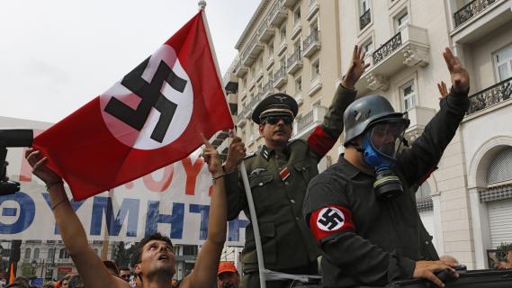Près de 25 000 manifestants, dont certainsdéguisés en soldats nazis, ont défilé dans les rues de la capitale grecque, le 9 octobre 2012, contre la visite de la chancelière allemande.