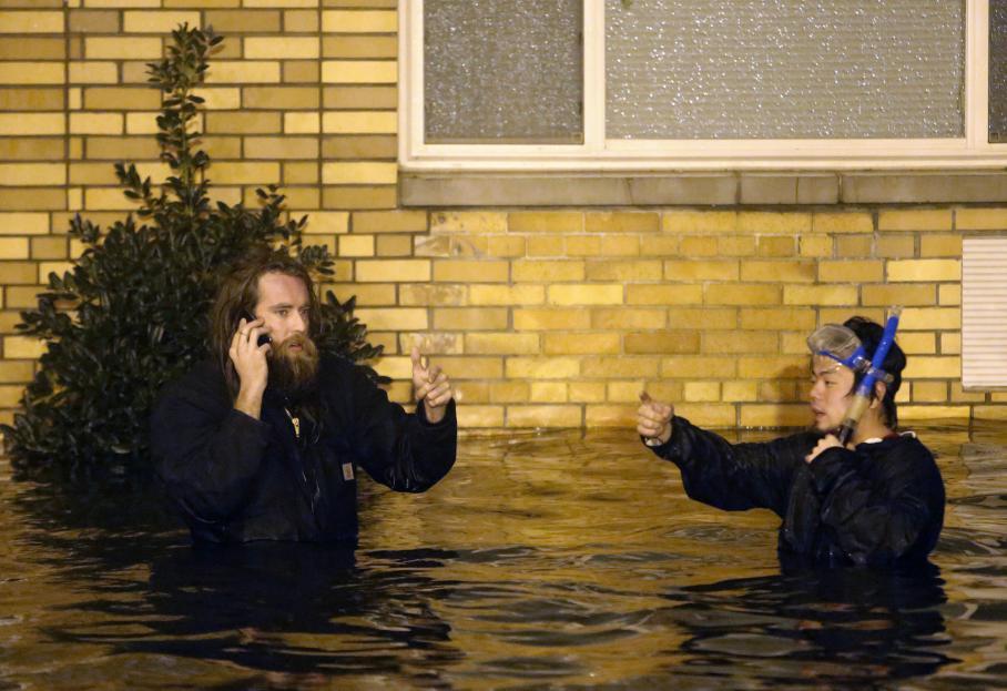 A Brooklyn (New York), deux amis sont sortis équipés dans les rues complètement inondées lundi 29 octobre 2012.