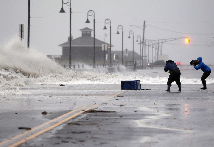 Malgré les recommendations des autorités, certains habitants se sont risqués dehors pour photographier l'évènement, comme ici à Cape May dans le New Jersey, point d'entrée de Sandy sur la côte.