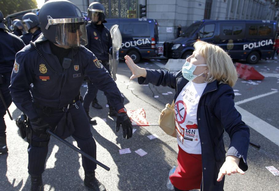 Un policier face à une manifestante lors de la mobilisation pour la grève générale du 14 novembre 2012, à Madrid (Espagne).