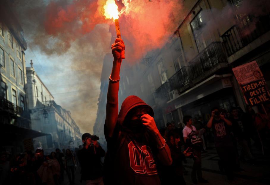 Un jeune manifestant tient une fusée de détresse dans les rues de Lisbonne (Portugal).