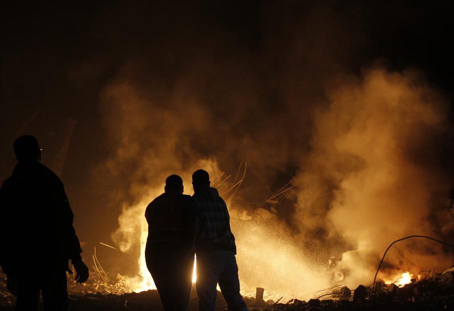 Des Palestiniens ont tenté d'éteindre le feu déclenché après un raid aérien dans la ville de Gaza, dans la nuit du mercredi 14 novembre 2012.