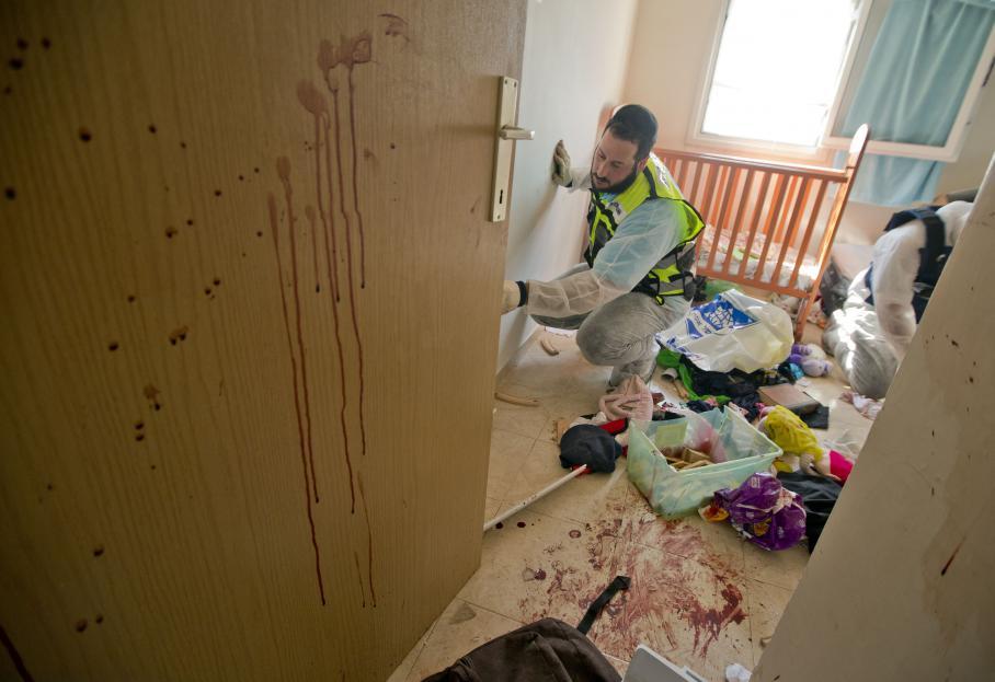 Des volontaires des services des urgences d'Israël nettoientune pièce de l'immeuble touché par une roquettetirée depuis la bande de Gaza jeudi 15 novembre 2012 à Kiryat Malachi.Trois personnes sont mortes dans cette attaque.