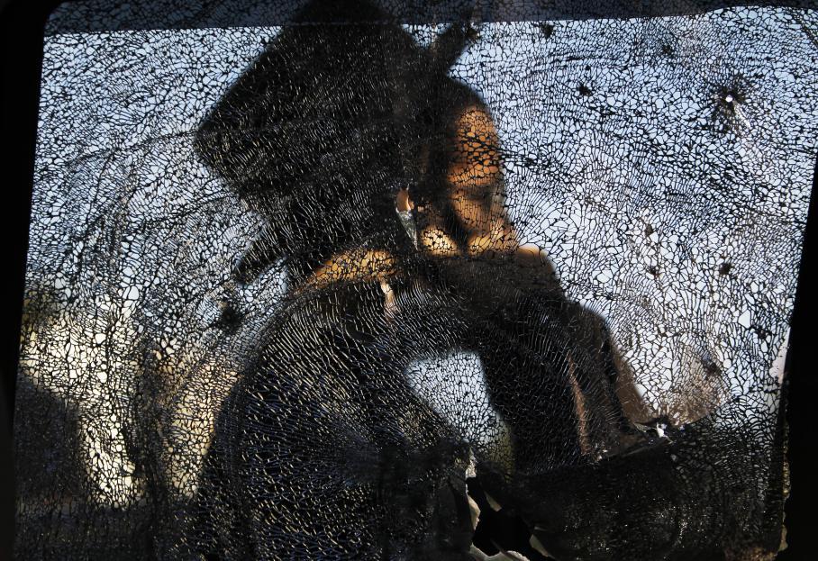 Un juif ultra-orthodoxe à Ashdod à travers la vitre brisée d'une voiture après le tir d'une roquette lancée de la bande de Gaza, vendredi 16 novembre 2012.