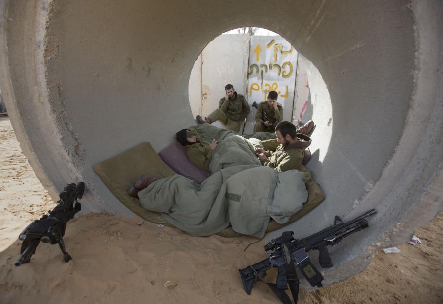 Des soldats israéliens se mettent à l'abri des tirs de roquette palestiniens dans la bande de Gaza,vendredi 16 novembre 2012.