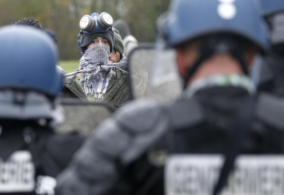 Un manifestant au visage dissimulé, fait face aux forces de l'ordre, déployées pour déloger les opposants du projet d'aéroport à Notre-Dame-des-Landes, vendredi 23 novembre 2012.