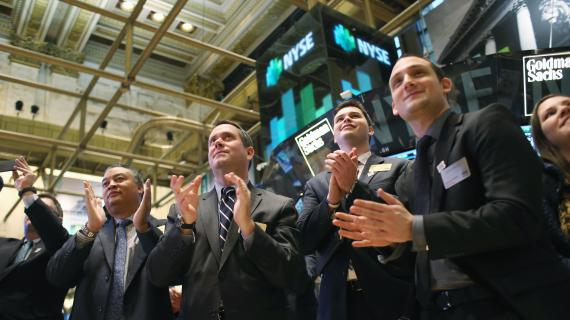 Des visiteurs applaudissent alors alors que rentitit la cloche qui annonce la clôture du New York Stock Exchange, le 24 janvier 2013. Wall Street frôle des sommets historiques.