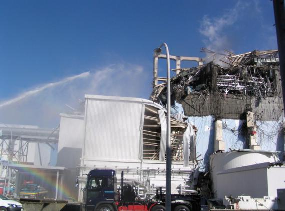 Des liquidateurs déversent de l'eau sur le réacteur 3 de la centrale de Fukushima (Japon), le 18 mars 2011.
