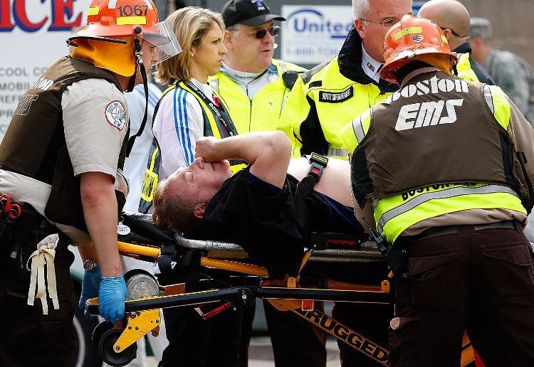 Un blessé est évacué après les explosions qui ont touchées le marathon de Boston, lundi 15 avril.