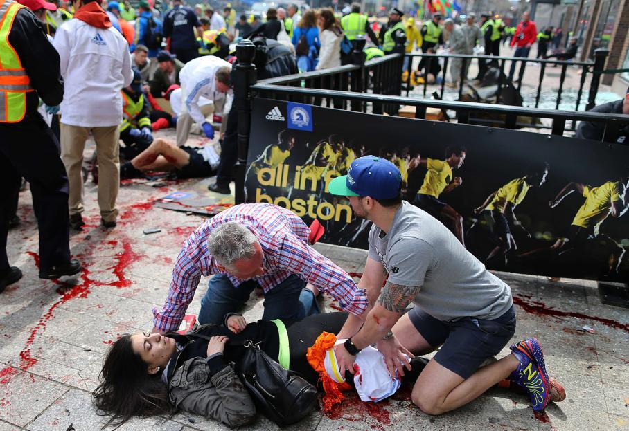 Deux hommes portent secours à une blessée tout près de la ligne d'arrivée du marathon.