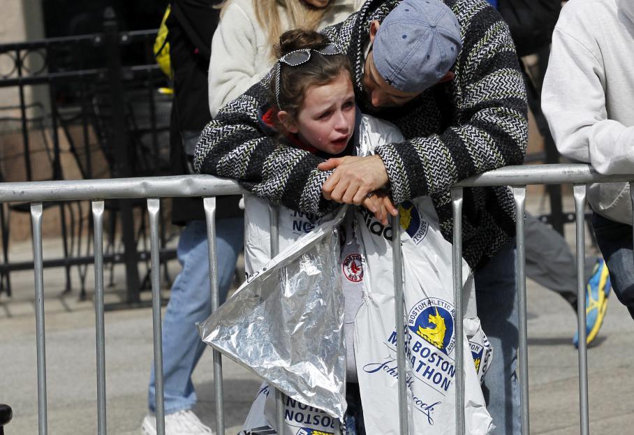 Un homme réconforte une enfant après les explosions près du parcours du marathon, peu après le drame.