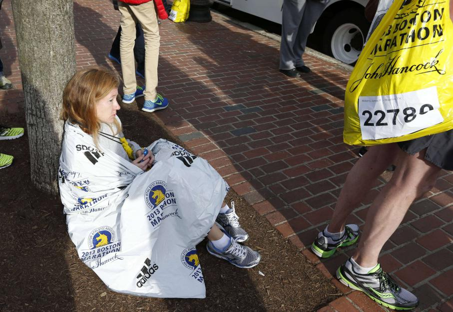 Une coureuse du marathon, choquée,se repose près de la ligne d'arrivée à Boston.
