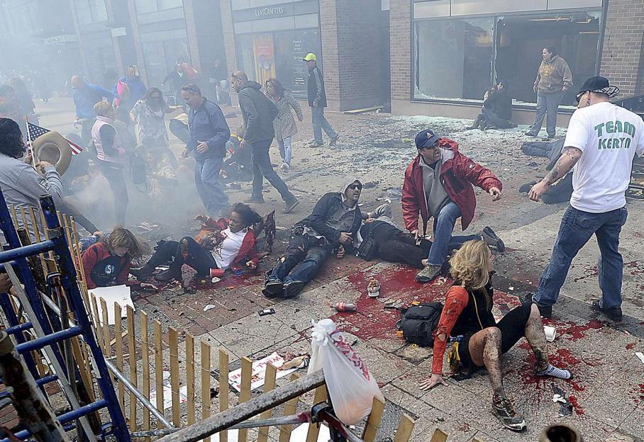 Des passants soufflés par le souffle de l'explosion, gisent à terre, encore sous le choc.