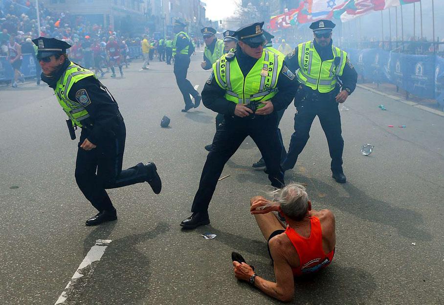 Le coureur Bill Iffrig, 78 ans, à terre alors que les policiers entendent la deuxième explosion et se précipitent.