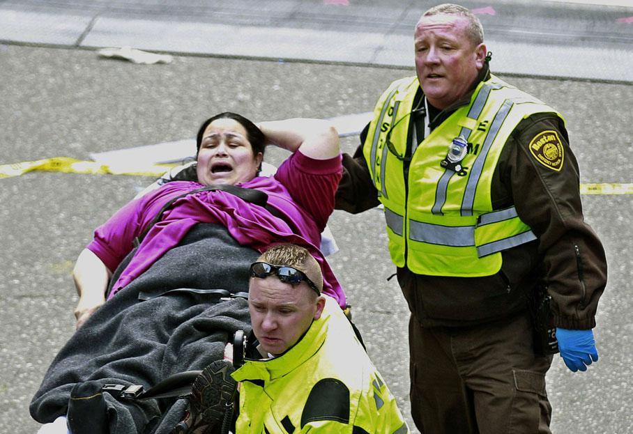 Des secouristes évacuent une femme blessée par une des deux explosions.