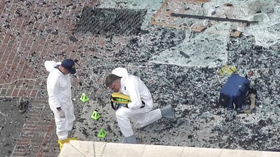 Des enquêteurs cherchent des indices, le 16 avril, autour du lieu de la première explosion qui a frappé Boston la veille.