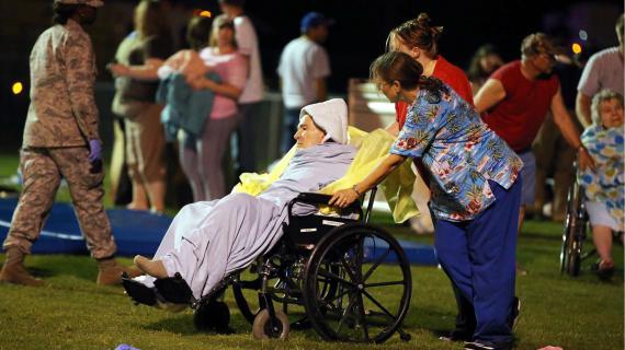 Du personnel médical transporte des personnes âgées dans un stade après l'explosion d'une usine d'engrais au Texas, près de la ville de Waco.