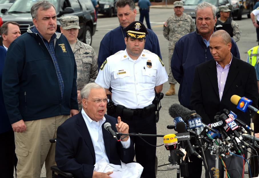 Le maire de Boston Thomas Menino (dans le fauteuil roulant) a donné une longue conférence de presse en milieu de journée le 19 avril 2013 pour annoncer que le plus jeune des suspects était toujours recherché.