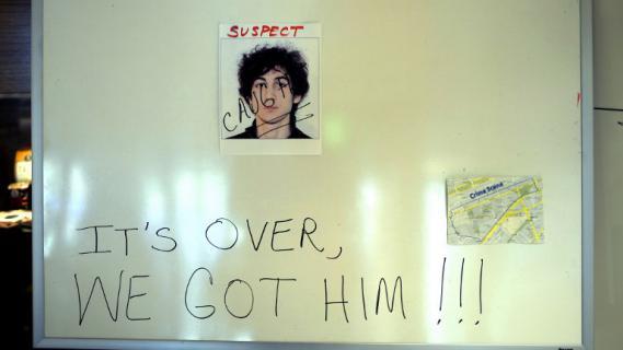 """""""C'est fini, nous l'avons eu !"""" Cette inscription est écrite sur un panneau où est affichée la photo de Djokhar Tsarnaev après son arrestation, samedi 20 avril 2013, à Boston (Etats-Unis)."""