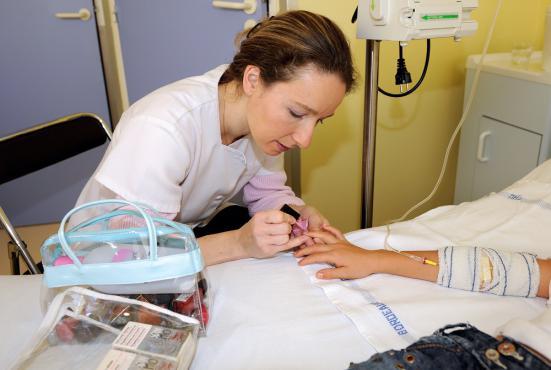 Une socio-esthéticienne vernit les ongles d'une patiente au CHU de Bordeaux, le 4 novembre 2008.