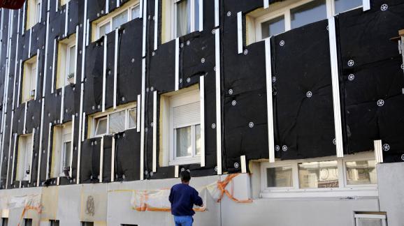 Un ouvrier installe des panneaux d'isolant sur la façade d'un immeuble à Nantes (Loire-Atlantique), le 25 mars 2013.