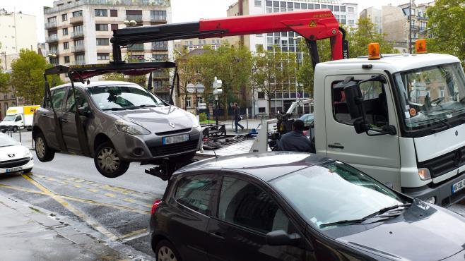 Une voiture est emmenée par la fourrière, le 17 octobre 2012, dans le 17e arrondissement de Paris.