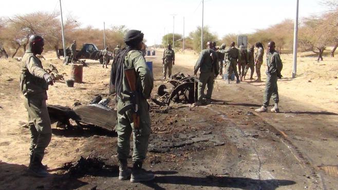 Des soldats maliens observent la scène après une attaque suicide menée par un jihadiste près de l'aéroport de Tombouctou au mali, le 21 avril 2013.