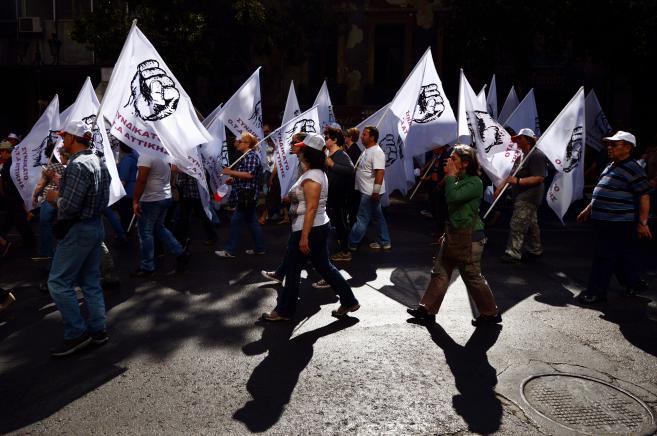 De nombreux Athéniens ont défilé, le 1er mai 2013, dans la capitale grecque, brandissant des drapeaux au poing levé.