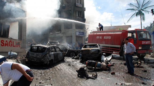 Des carcasses de voitures calcinées sont visibles sur le lieu du double attentat qui a frappé la ville de Reyhanli (Turquie), près de la frontière syrienne, le 11 mai 2013.