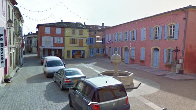 """La place de la mairie, où se trouve la maison """"Couloumiès"""", à Carla-Bayle (Ariège)."""
