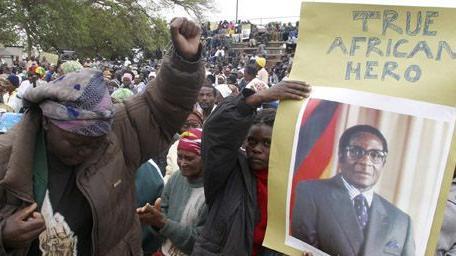 D\'anciens combattants de la guerre d\'indépendance chantent des slogans lors d\'une manifestation de soutien au président zimbabwéen, Robert Mugabe, le 11-10-2007, Sur la pancarte, au-dessus de sa photo, on peut lire en anglais: «Vrai héros aficain».