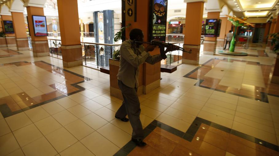Un policier kényan armé à la recherche des hommes armés et masqués qui ont ouvert le feu samedi 21 septembre 2013 sur les clients et le personnel d'un centre commercial de luxe à Nairobi (Kenya).