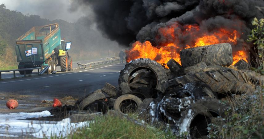Des agriculteurs bretons brûlent des pneus près de la route, le 14 octobre, lors d'une manifestation à Morlaix (Finistère) en compagnie de salariés de différentes entreprises agroalimentaires.