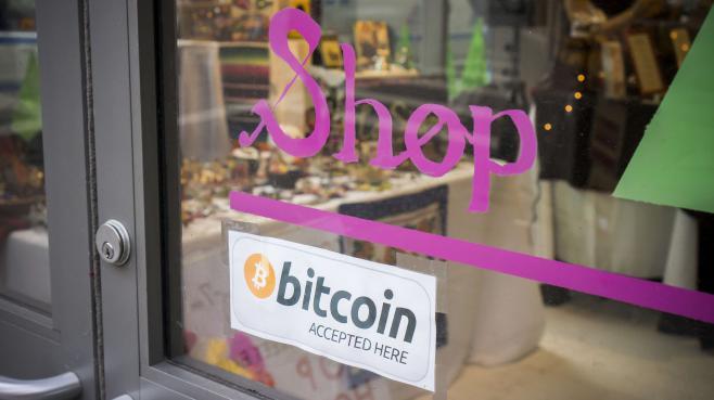 Une affichette sur un magasin new-yorkais indique qu'il accepte les paiements en bitcoins.