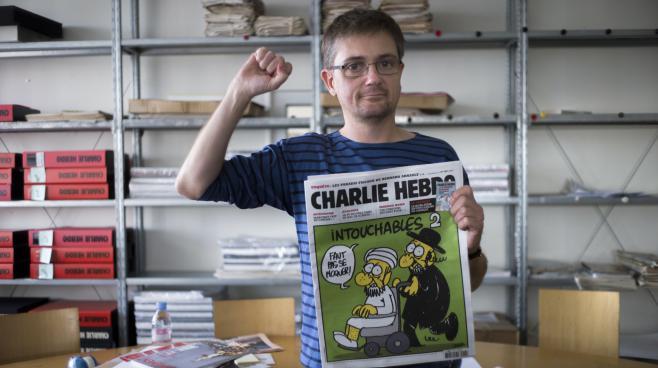"""Charb, le directeur de la publication de """"Charlie Hebdo"""", tient un exemplaire de l'édition à l'origine de la plainte déposée par deux associations, le 19 septembre 2012 à Paris."""