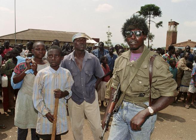 Des miliciens hutus assistent à l'évacuation, par les Nations unies, de 400 Tutsis de l'église de la Sainte-Famille, à Kigali,le 13 juin 1994.