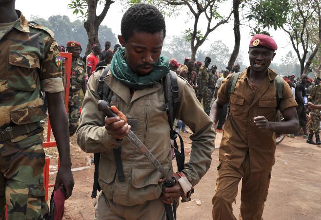 Un membre des forces armées centrafricaines (FACA) range son arme après le lynchage d'un homme soupçonné d'entre un ancien rebelle de la Seleka, le 5 février 2014 à Bangui (Centrafrique).