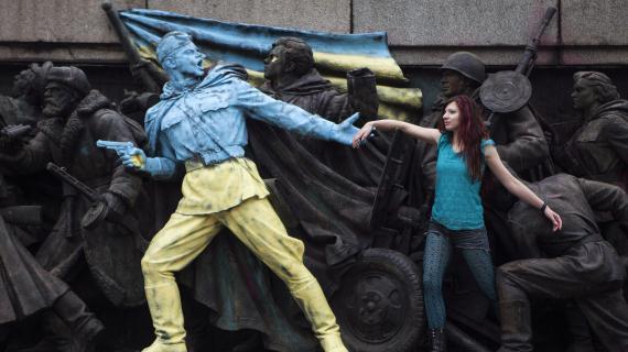 Une femme pose devant un monument représentant des soldats soviétiques et repeint aux couleurs de l'Ukraine à Sofia (Bulgarie), le 23 février 2014.
