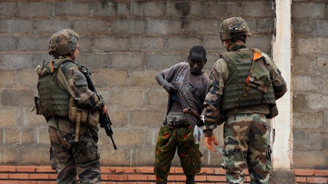 Deux soldats français contrôlent un homme dans le quartier PR4 de Bangui (Centrafrique), le 27 février 2014.