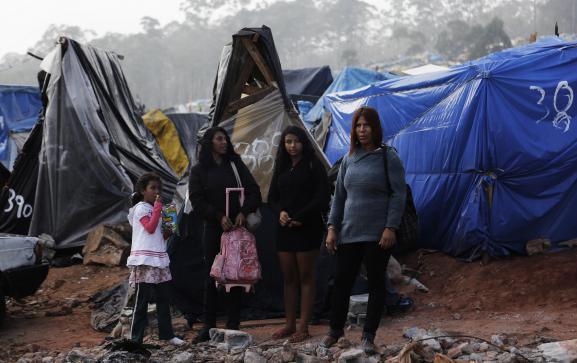Une famille pose dans le campdu Mouvement des travailleurs sans toit (MTST), à Sao Paulo (Brésil), le 15 mai 2014.