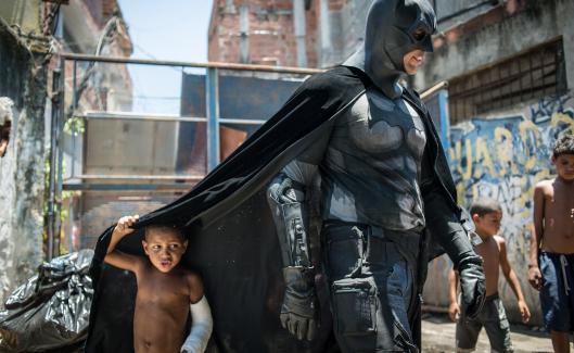 Des enfants de la favela de Metrô-Mangueira, à Rio de Janeiro (Brésil), posent avecEron Morais de Melo, un militant déguisé en Batman, qui proteste contre la destruction de maisons dans le cadre des travaux de la Coupe du monde de football, le 9 janvier 2014.