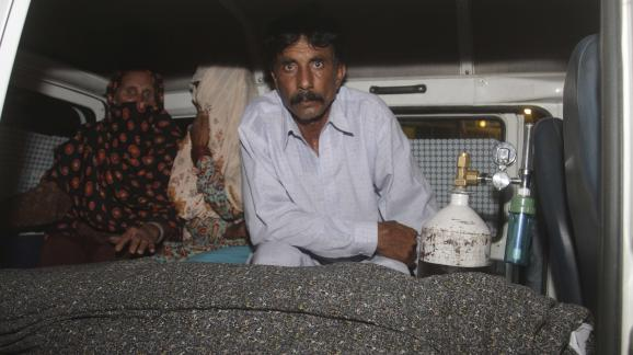 Mohammad Iqbal aux côtés de sa femme enceinte lapidée à mort, dans une ambulance, mardi 27 mai à Lahore (Pakistan).