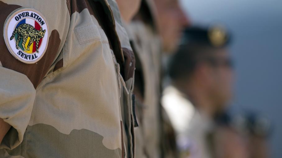 Des soldats de l'opération Serval au Mali écoutent le ministre de la Défense, Jean-Yves Le Drian, prononcer un discours, le 31 décembre 2013 à Gao (Mali).