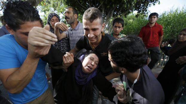 Des proches des enfants tués le 16 juillet 2014 sur une plage après un bombardement israélien s'écroulent de chagrin, à Gaza.
