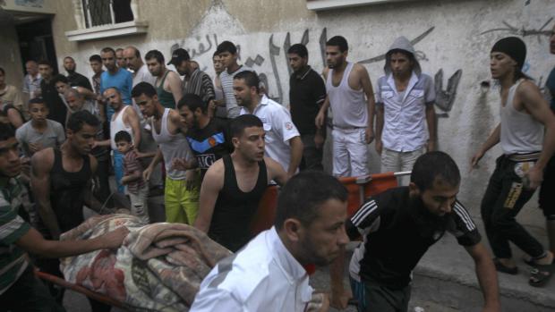 Des secouristes transportent un corps extrait des décombres d'un immeuble détruit par un bombardement israélien, le 25 juillet 2014s à Rafah, dans la bande de Gaza.