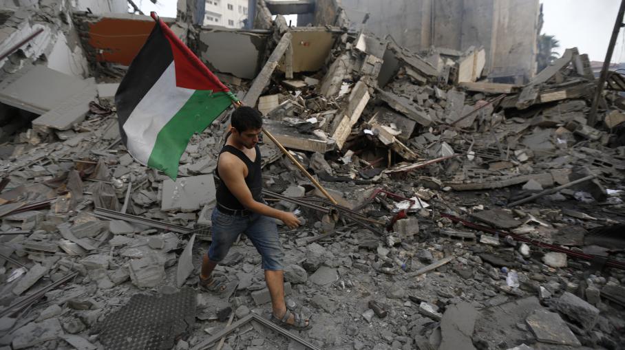 Un habitant de la bande de Gaza sort un drapeau palestinien des décombres, après une frappe israélienne sur Gaza, le 26 août 2014.
