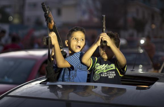 Deux enfants brandissent des armes pour célébrer le cessez-le-feu dans les rues de Gaza, mercredi 26 août.